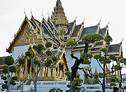 At the Grand Palace in Bangkok, Thailand, Dusit Maha Prasat Hall rises behind the small pavillion of Aphorn Phimok Prasat, which was built entirely of wood by King Rama IV. Dusit Maha Prasat throne hall was built by King Rama I in 1790, as a lying-in-state of kings, queens, and honored members of the royal family. It also supports the annual Coronation Day ceremony. A topiary garden of sculpted living trees grows in the foreground. The Grand Palace complex (Phra Borom Maha Ratcha Wang) was built on the east bank of the Chao Phraya River starting in 1782, during the reign of Rama I. It served as the official residence of the king of Thailand from the 1700s to mid 1900s.