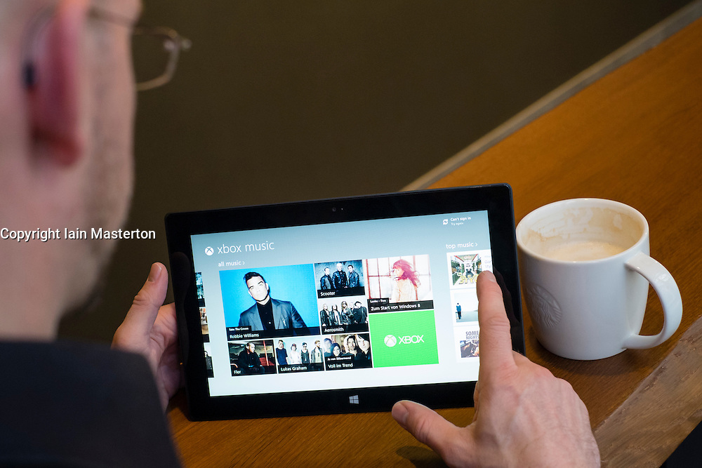 Man browsing Xbox music store on a Microsoft Surface rt tablet computer in a cafe
