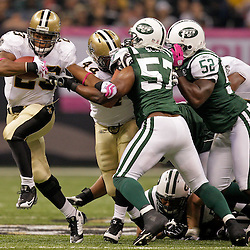 2009 October 04: New Orleans Saints running back Pierre Thomas (23) runs by New York Jets linebacker Bart Scott (57) during a 24-10 win by the New Orleans Saints over the New York Jets at the Louisiana Superdome in New Orleans, Louisiana.