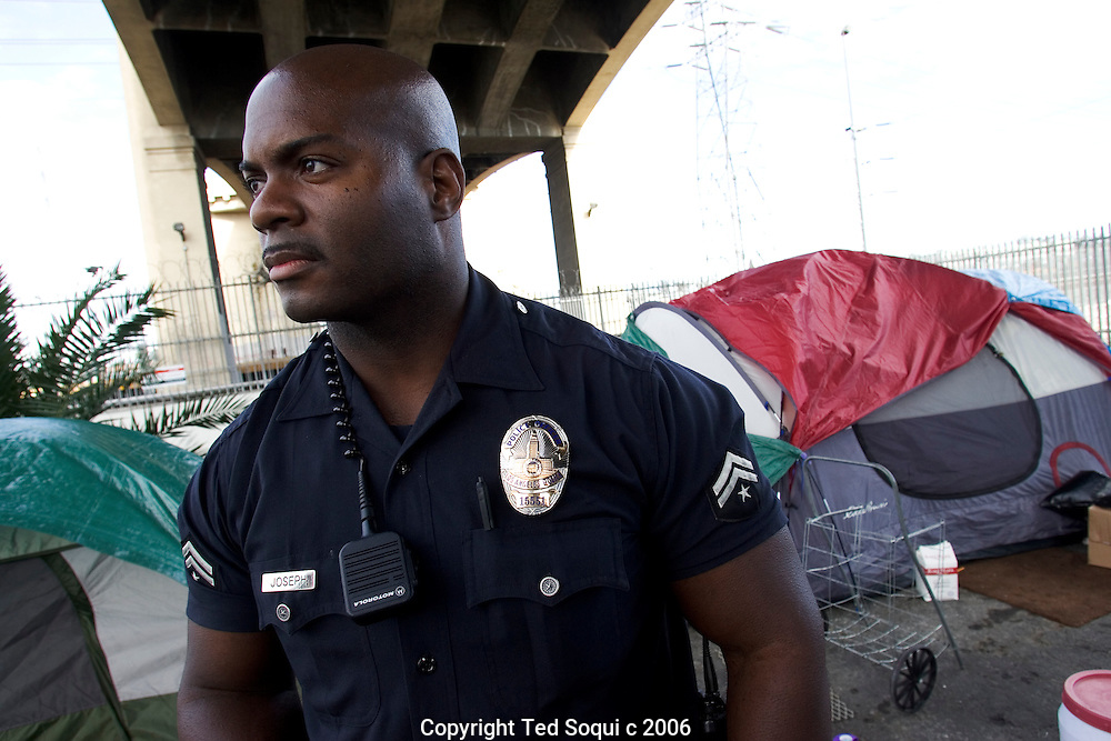 Senior Lead Officer Deon Joseph in front of a small homeless encampment under LA's Sixth Street Bridge.