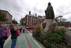 Tourists take photographs of a statue of Roger Conant dressed in a robe and top hat, Salem, Massachusetts, United States of America