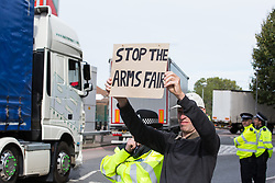 London, UK. 5 September, 2019. An activist holds up a sign reading 'Stop The Arms Fair' outside ExCel London during protests on the fourth day of a week-long carnival of resistance against DSEI, the world's largest arms fair.