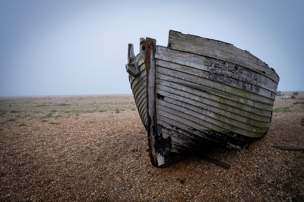 A derelict fishing boat sits on the shingle beach in Dungeness on a misty winters day, on the 25th of January 2020, Dungeness, Kent, United Kingdom. Dungeness is a shingle beach on the coast in Kent, famous for the Dungeness Power Station and Derek Jarman's Prospect Cottage.  (photo by Andrew Aitchison / In pictures via Getty Images)