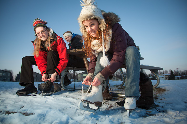 Covenant House voluteers, Rose Aspholm, Lauren Bajda, and Monica Stoesser, strap on their skates for the first skate of the season at Westchester Lagoon, Anchorage.