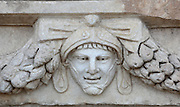 Mask and garland frieze from the Portico of Tiberius on the Southern portico of the Agora, 1st century AD, Aphrodisias, Aydin, Turkey. The Sculpture School at Aphrodisias was an important producer of carved marble sarcophagi and friezes from the 1st century BC until the 6th century AD. The Portico of Tiberius was built under the reign of Tiberius and has many examples of mask and garland friezes, consisting of the heads of gods, goddesses, theatrical characters, mythological figures or masks, each with a distinct facial expression, between hanging garlands of leaves, fruit and flowers. This example shows a young man wearing a helmet with a happy smiling expression. Aphrodisias was a small ancient Greek city in Caria near the modern-day town of Geyre. It was named after Aphrodite, the Greek goddess of love, who had here her unique cult image, the Aphrodite of Aphrodisias. The city suffered major earthquakes in the 4th and 7th centuries which destroyed most of the ancient structures. Picture by Manuel Cohen