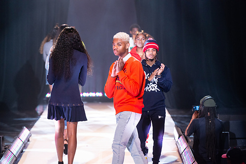 Several models, all clapping, entering and exiting the runway from behind a curtain at the Howard University Annual Fashion Show.