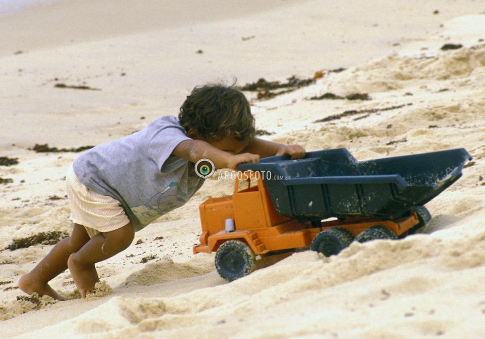 Trancoso,BA.Agosto,1999.Crianca brincando na areia com caminhao./ Child playing with atoy.Foto Marcos Issa/Argosfoto