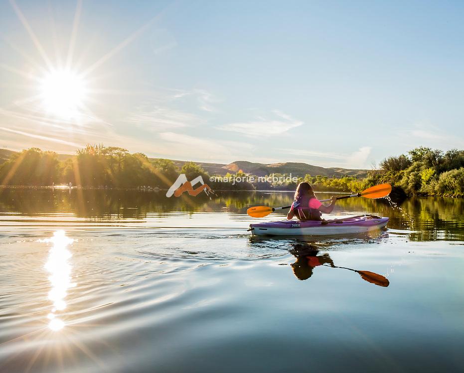 Woman kayaking the Snake River near sunset Hagerman, Idaho. MR