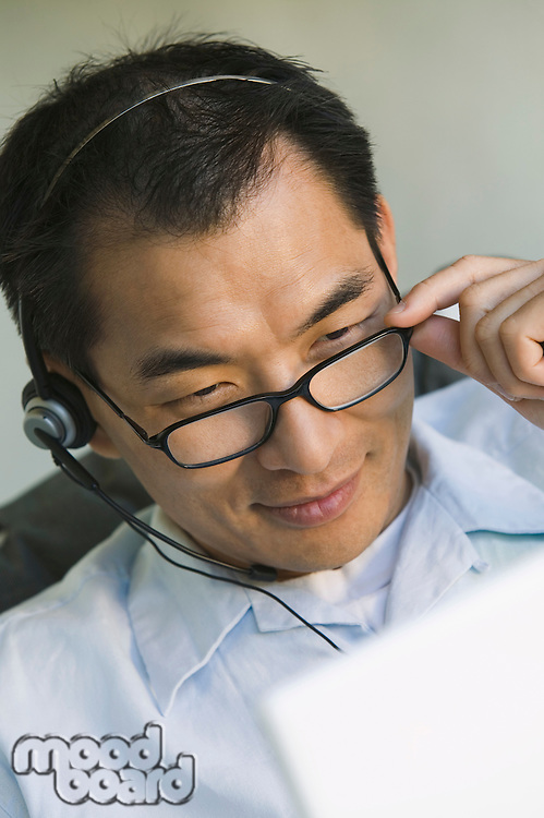 Businessman Wearing Headset and Using Laptop