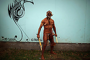 A man displays his body tattooed in volcanic mud, an ancestral technique, as he poses for a photo aside a stylized graffiti depicting a bird, symbol of the Rapa Nui culture during a festival named Tapati Rapa Nui in Hanga Roa, Rapa Nui, Saturday, Feb. 12, 2011. As Chile  tries to push globalization into the island with the same power the Pacific waves reach its rocky shores, boundaries of race become blurrier in the most important Polynesian island, and during the Tapati festival, a former native week long celebration, only blue eyed or really white skinned people can be spotted like foreigners.