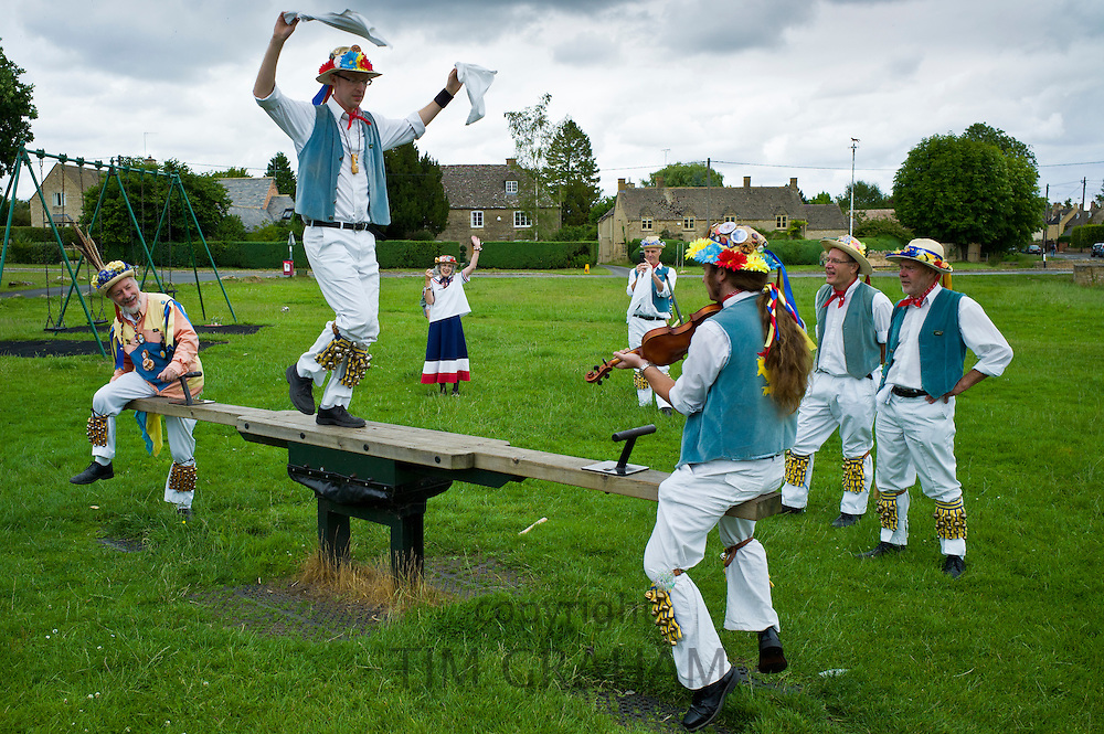 Morris dancers, Icknield Way Morris Men, in children's playground at The Kings Head Pub, Bledington, Oxfordshire, UK