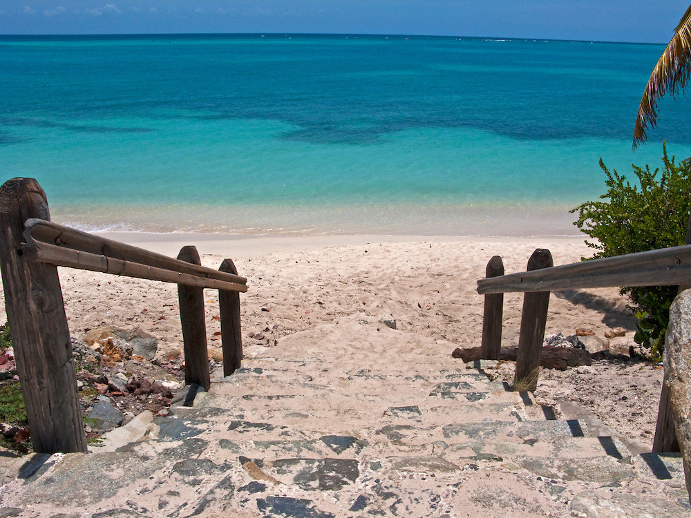 Wooden rails leads to a white sandy beach in Aruba.