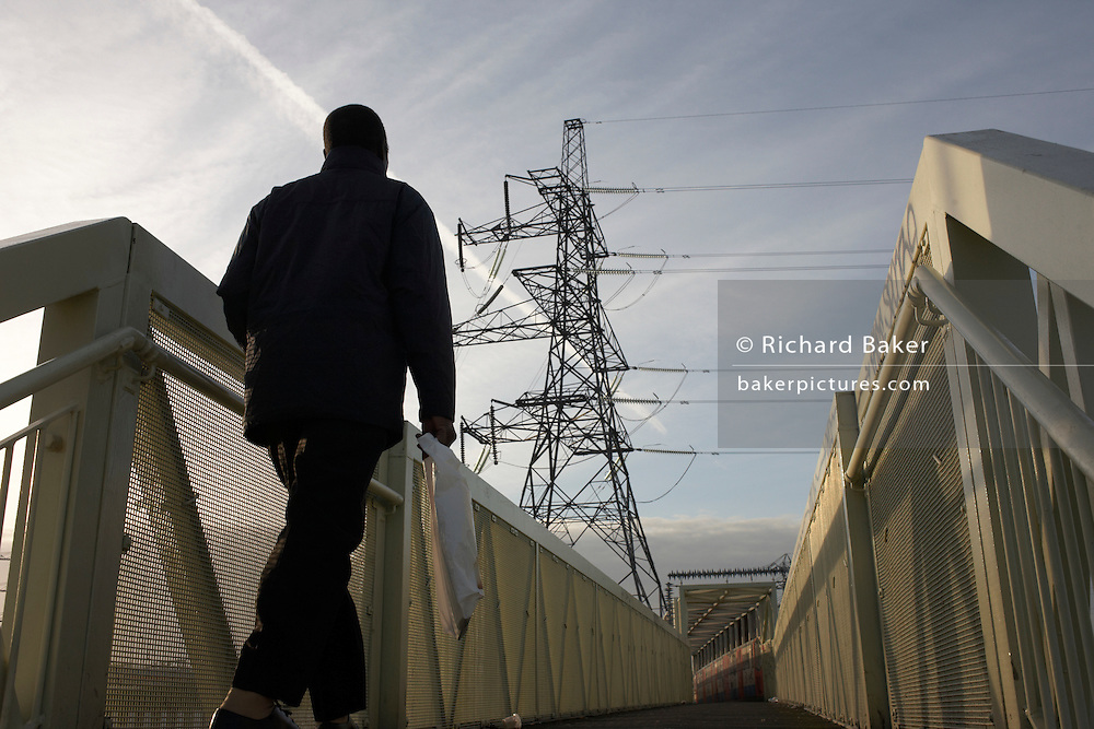 A pedestrian walks towards a walkway and electricity pylon near West Ham substation, Canning Town, London