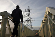 A pedestrian walks towards a walkway and electricity pylon near West Ham substation, Canning Town, London