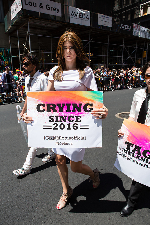 """New York, NY - 30 June 2019. The New York City Heritage of Pride March filled Fifth Avenue for hours with participants from the LGBTQ community and it's supporters. A participant costued as Melania Trump carries a sign reading """"Crying Since 2016."""""""