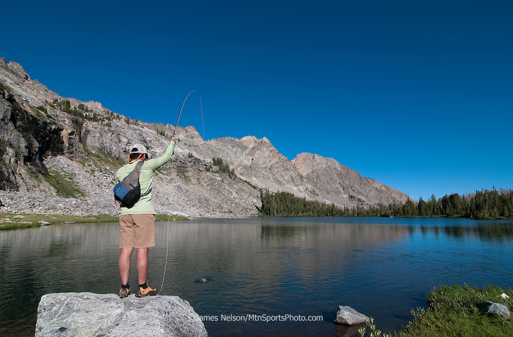 A fly fisherman plays a westslope trout on an alpine lake named  Kane Lake in the Pioneer Mountains of Idaho.