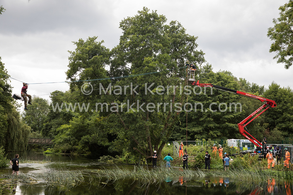Denham, UK. 24 July, 2020. Environmental activists from HS2 Rebellion, including Swan on a line above the shallow river Colne, try to protect an ancient alder tree from destruction in connection with works for the HS2 high-speed rail link in Denham Country Park. A large policing operation involving the Metropolitan Police, Thames Valley Police, City of London Police and Hampshire Police as well as the National Eviction Team was put in place to enable HS2 to remove the tree.