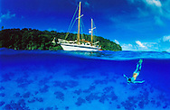 Underwater split level view of a  snorkeller off a charter yacht enjoys the clear blue water at a calm anchorage in the Vava'u islands, Tonga. South Pacific. To use this image please contact Getty Images. Getty #BB6280-001