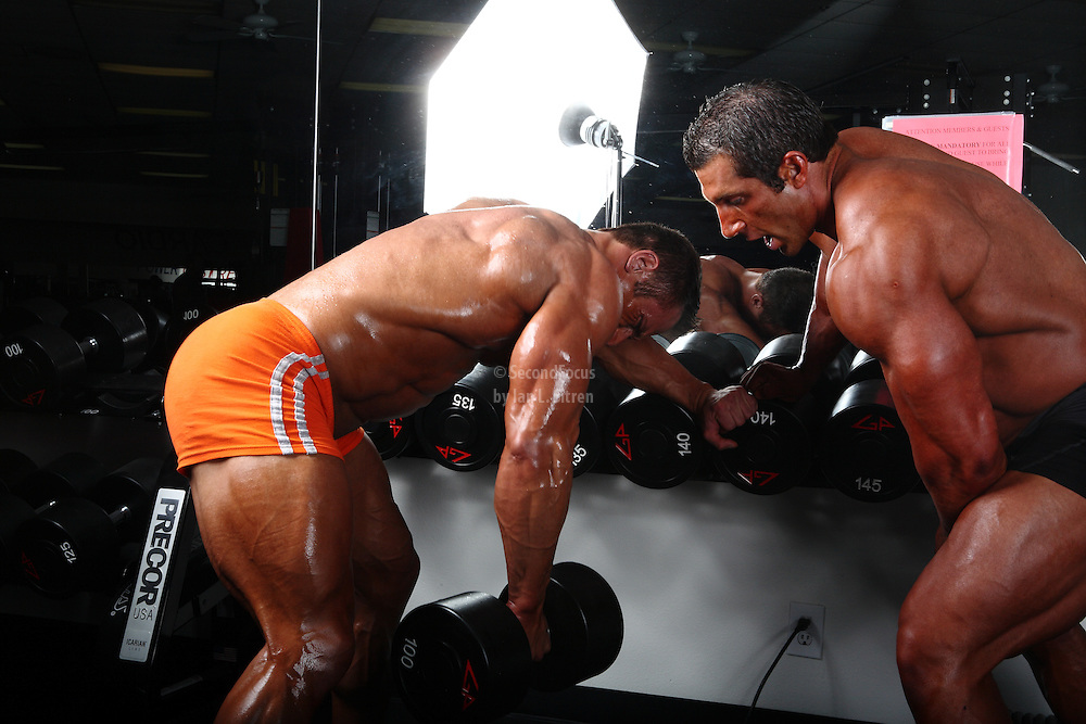 Bodybuilders Dan Decker and Brian Yersky doing one arm dumbbell rows.