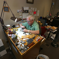 Scott sits at his work talbe getting his day started repairing a variety of watches, helping customer with purchases and taking a few phone calls.