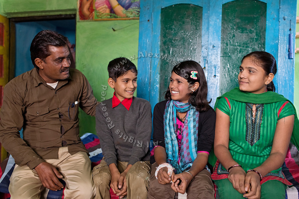 Ritu Gaur, 13, (centre/right) is sitting with her father, Sanjay, 45, (left) her younger brother, Pawan, 11, and her older sister, Malti, 17, (right) insider their home in Chittawaliya village, rural Sehore,  Ritu lives in the Jamoniya Tank Girls Hostel by her school, near Sehore, Madhya Pradesh, India, where the Unicef India Sport For Development Project has started in 2012. Covering 313 state-run girls' hostels and 207 mixed hostels in Madhya Pradesh, the project ensures that children from Scheduled Tribes (ST) and others amongst the poorest people in India, can easily access education and be introduced to sports. Field workers from Unicef also oversee their nutrition and monitor the overall conditions of each pupil.