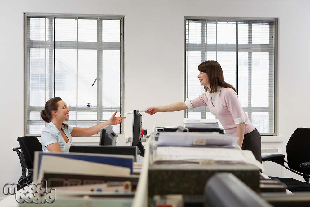 Two women in office one handing documents to other over desk side view