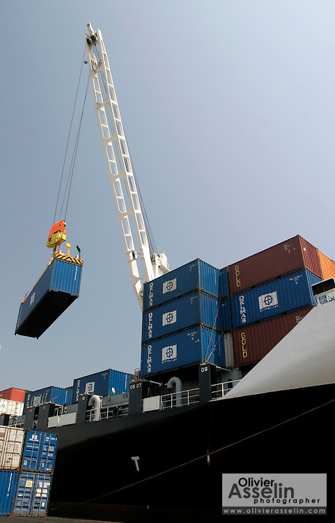 Crane loading containers on boat at harbour in Tema, Ghana.