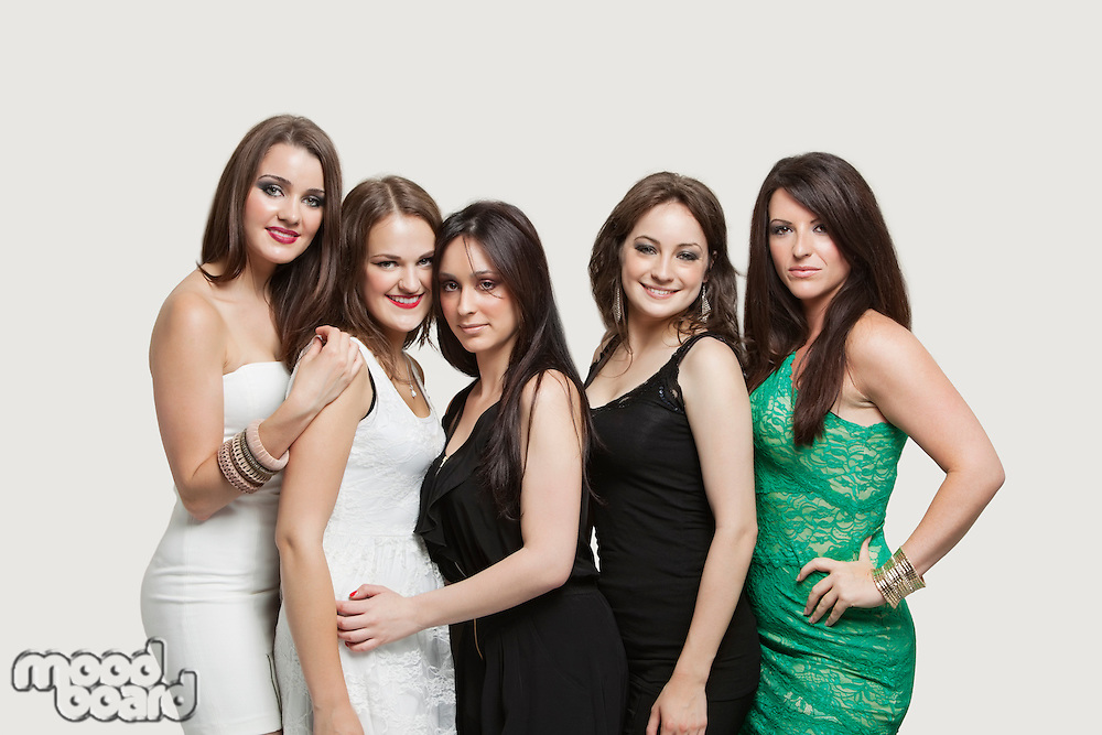 Portrait of five young women posing together over gray background