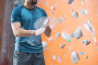 Midsection of man dusting powder by climbing wall in crossfit gym