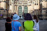 "A ""just married"" couple - surrounded by tourists - is getting photographed in front of St. Vitus Cathedral in Prague. The house of worship is a Roman Catholic metropolitan cathedral on the area of the Prague Castle complex and the seat of the Archbishop of Prague."