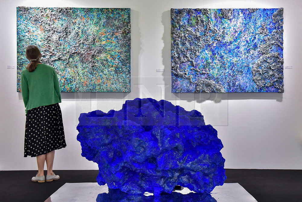 """© Licensed to London News Pictures. 27/06/2017. London, UK.  (L to R) """"The Earth-XVII"""", """"Out of the Space III"""" and """"The World - IX"""" all by Victoria Kovalenchikova at The Arts & Antiques Fair taking place at Olympia in Kensington.  The event is the UK's largest and most established art and antiques fair and runs until 2 July.  Photo credit : Stephen Chung/LNP"""