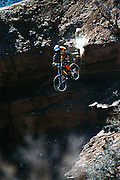 Andrew Mills drops down the Canadian Bacon line at the 2002 Red Bull Rampage freeride mountain bike competition in Virgin, Utah.