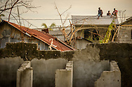 Young men perch on a rooftop amongst damage caused from Hurricane Matthew on Tuesday, Oct. 11, 2016, in Les Cayes, Haiti. LCMS Communications/Erik M. Lunsford