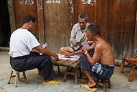 Chine. Province du Guizhou. Marche dans les environs de Congjiang. Miao Noir. Joueur de carte. // China. Guizhou province. Market around Congjiang. Black Miao ethnic group. Card player.