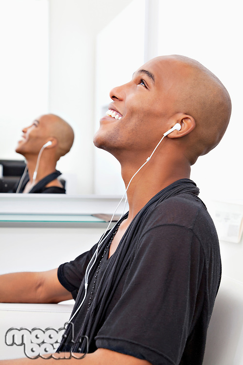 Profile view of man listening music at salon