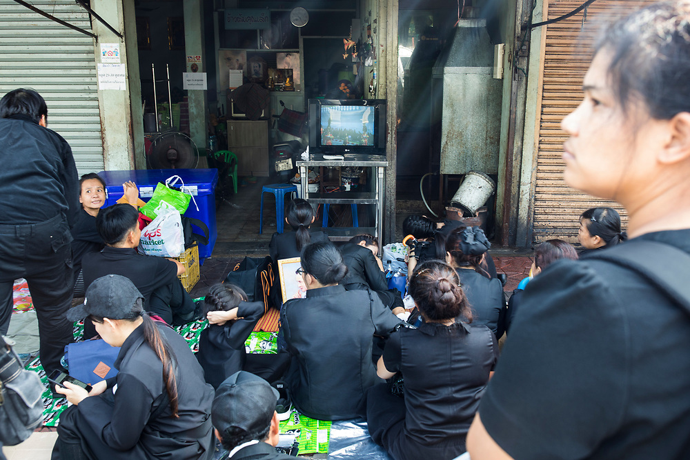 BANGKOK, THAILAND - October 26, 2017: Unable to get close to the Grand Palace, crowds of people gather around an outdoor television to watch the late king's funeral procession in Bangkok, Thailand. Hundreds of thousands of people, dressed in black, have gathered in Bangkok over a year after the death of Thailand's popular King Bhumibol Adulyadej.  The five-day royal cremation ceremony is taking place between October 25-29 in Bangkok's historic Grand Palace and the Sanam Luang area.