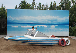 epa02909288 A Chinese boy plays on a motor boat with a seaview backdrop in a park of Beijing, China on 11 September 2011.  EPA/HOW HWEE YOUNG