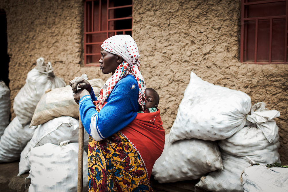 A woman and her baby stand close to bags of Irish potatoes, bagged up ready to be sold. Shingiro District, Rwanda