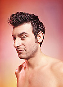 """Male actor posing topless sporting a """"pompadour"""" hairstyle as he stares back at the camera."""