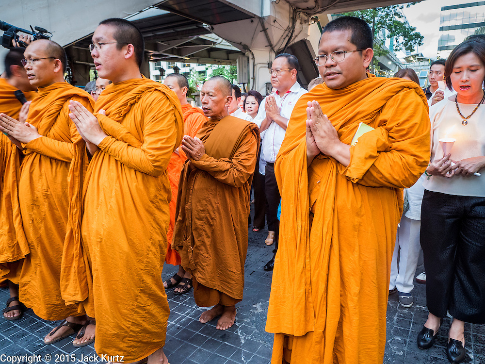 24 AUGUST 2015 - BANGKOK, THAILAND: Buddhist monks lead a candlelight procession to Erawan Shrine during a memorial for victims of the bombing at the Shrine. One week after the a bomb at the Erawan Shrine in the center of Bangkok killed dozens and hospitalized scores of people, police have not made any arrests. Police bomb sniffing dogs have been deployed to malls and markets around Bangkok. There was a large memorial service sponsored by businesses close the bomb site Monday evening.    PHOTO BY JACK KURTZ