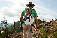 A man carries a backpack with a bra attached to the outside as he hikes up Bald Mountain in Lake Cowichan, BC, on Vancouver Island.