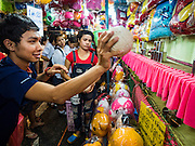 20 NOVEMBER 2015 - BANGKOK, THAILAND:   Students play a ball game on the midway at the Wat Saket temple fair. Wat Saket is on a man-made hill in the historic section of Bangkok. The temple has golden spire that is 260 feet high which was the highest point in Bangkok for more than 100 years. The temple construction began in the 1800s in the reign of King Rama III and was completed in the reign of King Rama IV. The annual temple fair is held on the 12th lunar month, for nine days around the November full moon. During the fair a red cloth (reminiscent of a monk's robe) is placed around the Golden Mount while the temple grounds hosts Thai traditional theatre, food stalls and traditional shows.   PHOTO BY JACK KURTZ