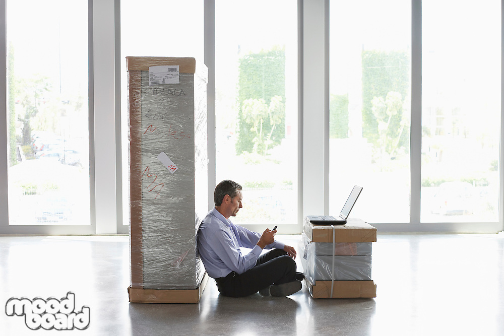 Man using mobile phone and laptop between packages in empty office