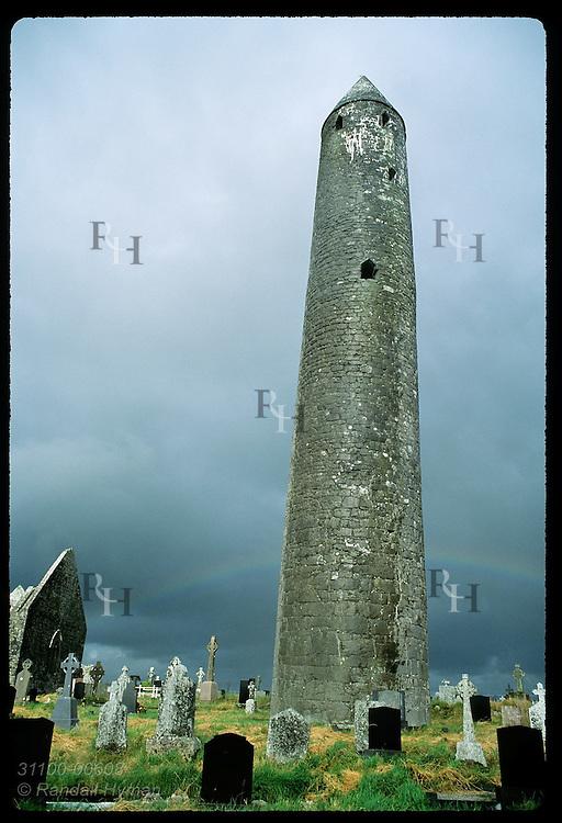 Kilmacduagh round tower (112') looms above rainbow & cemetery @ St Colman monastery site; Gort Ireland