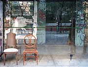 Two old chairs have been put at a bus stop in Hell's Kitchen along 9th Avenue in Manhattan, New York City.