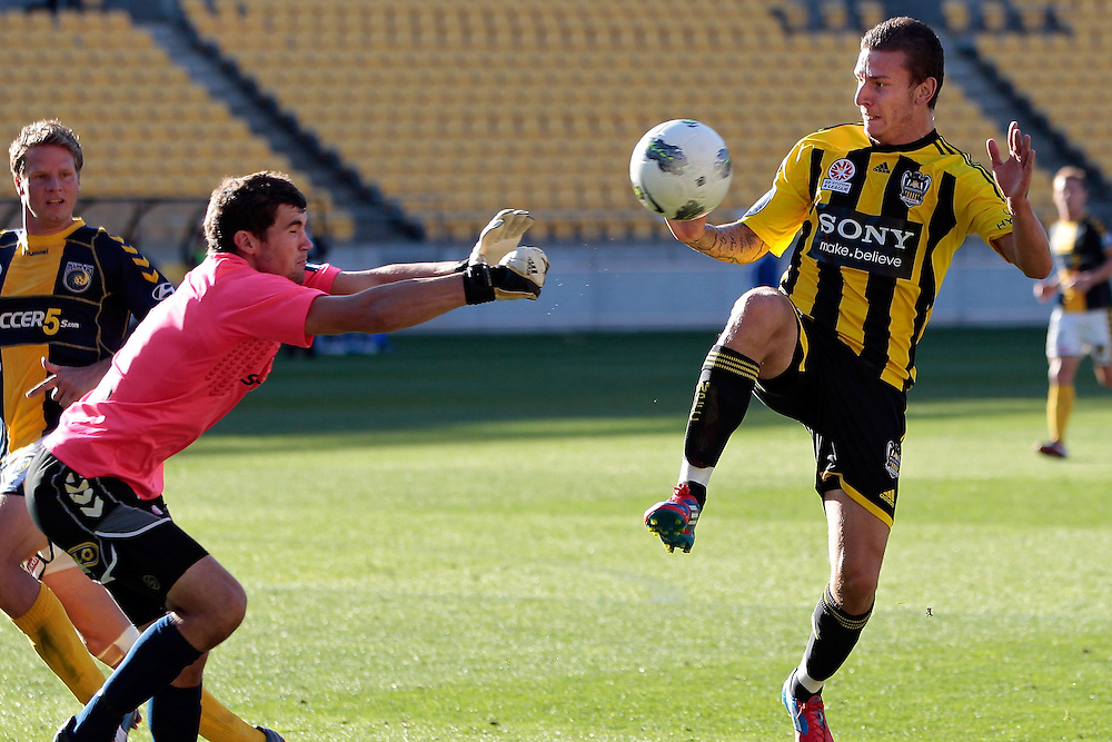 Mariners' goalie Mathew Ryan, left, punches the ball back past Phoenix's Mirjan Pavlovic in the A-League football match at Westpac Stadium, Wellington, New Zealand, Sunday, March 25, 2012. Credit: SNPA/Dean Pemberton