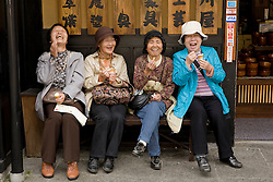 Asia, Japan, Gifu prefecture, Takayama (also known as Hida-Takayama), women laughing and eating ice cream on bench