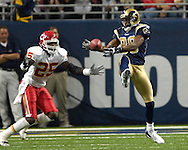 St. Louis Rams wide receiver Isaac Bruce (80)reaches behind him to pull in a pass from quarterback Marc Bulger for 23-yards, in front of Kansas City Chiefs safety Greg Wesley (25)at the Edward Jones Dome in St. Louis, Missouri, November 5, 2006.  The Chiefs beat the Rams 31-17.<br />
