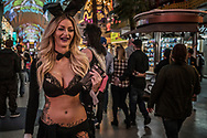 Woman, dressed as a Playboy bunny, takes a break from posing for photos with tourists on the old strip, Fremont Street in Las Vegas.  Nevada