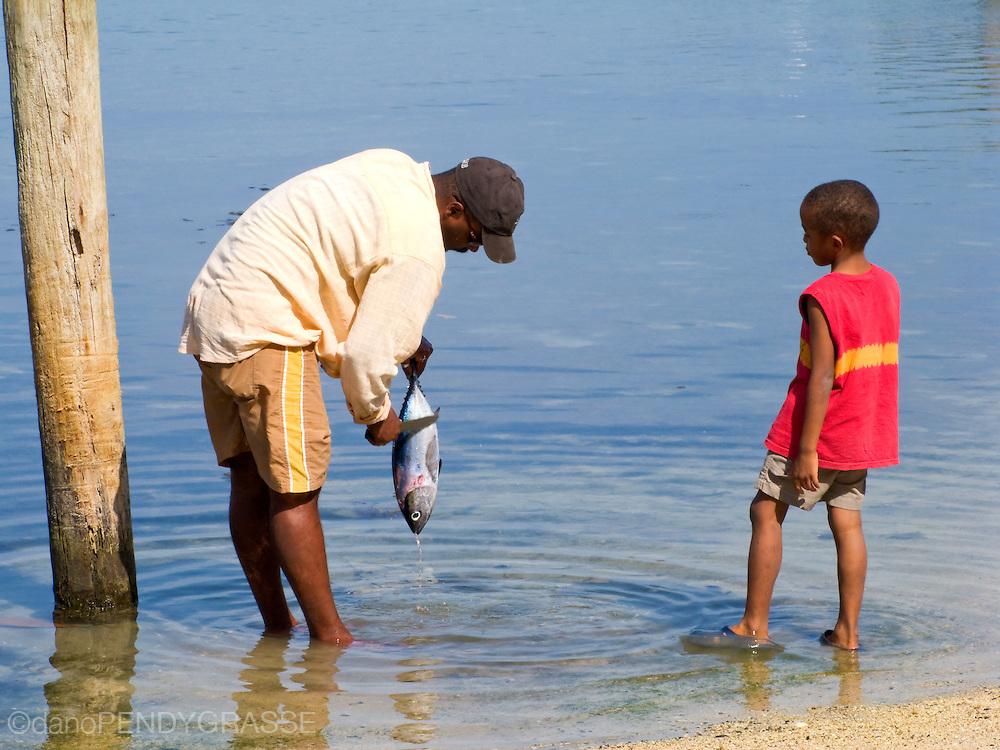 A man shows his boy how to clean a tuna fish on the Caribbean island of Roatan, Honduras.